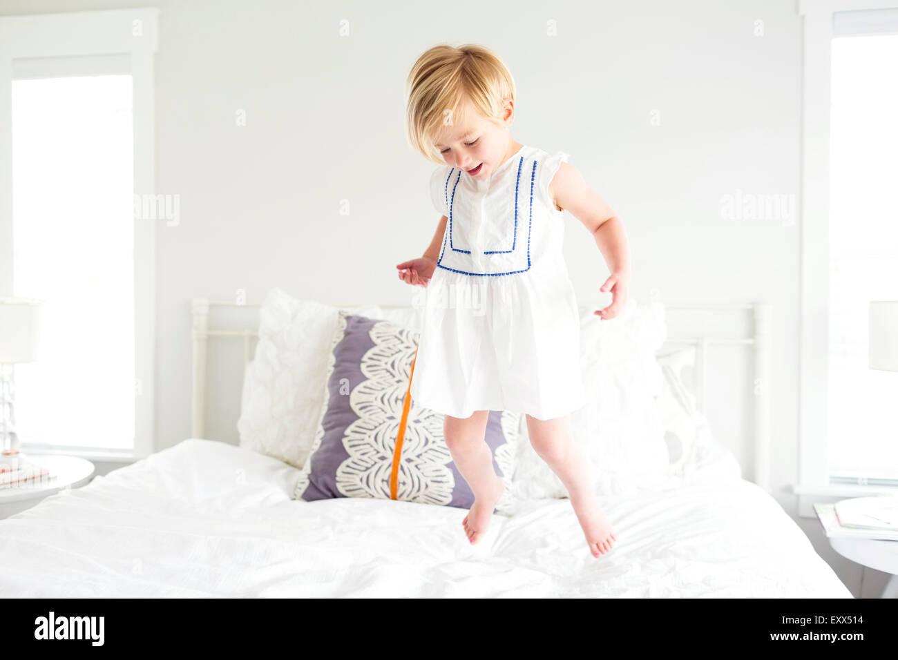 Mädchen (2-3) springen auf Bett Stockbild