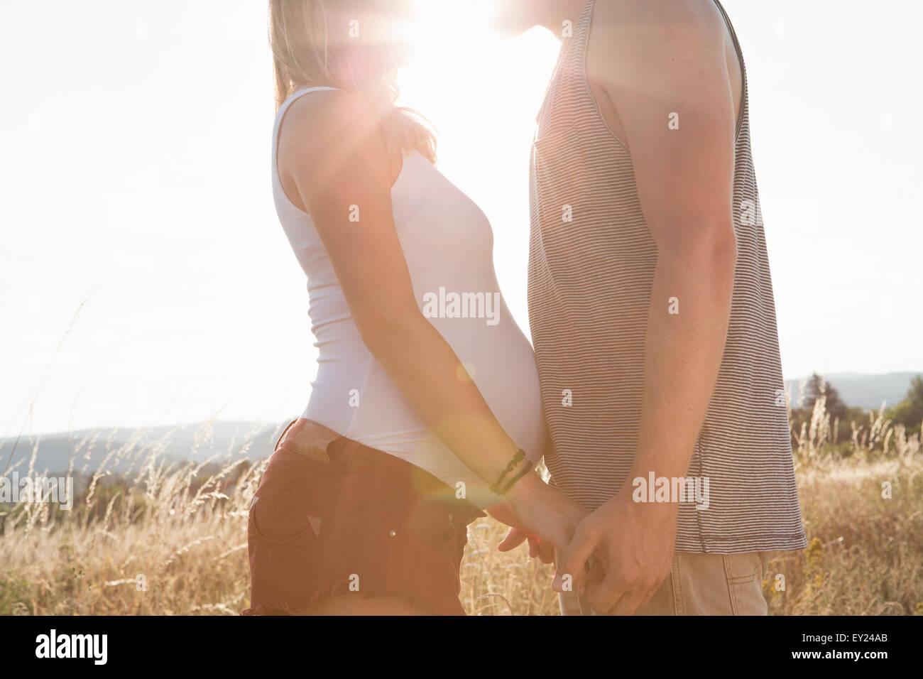 Junger Mann und Schwangere Freundin von Angesicht zu Angesicht und halten Hände in Feld Stockbild