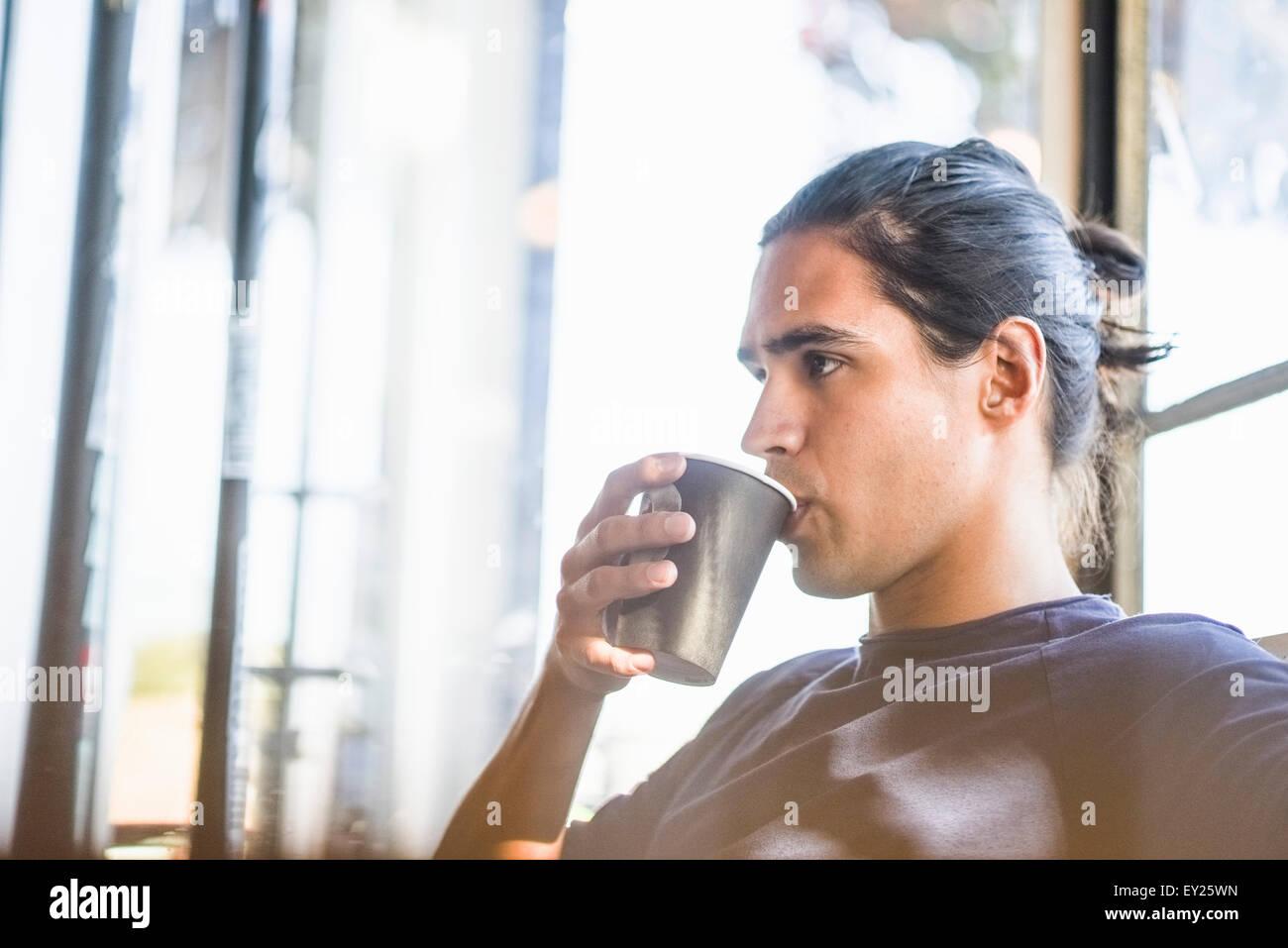 Junger Mann, Kaffee trinken, drinnen Stockbild