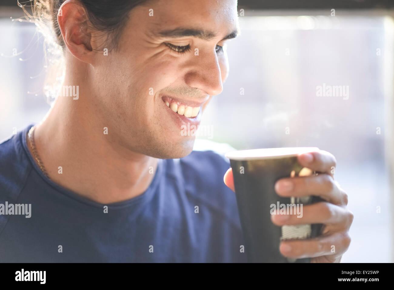 Junger Mann, der Kaffeetasse, drinnen hält Stockbild