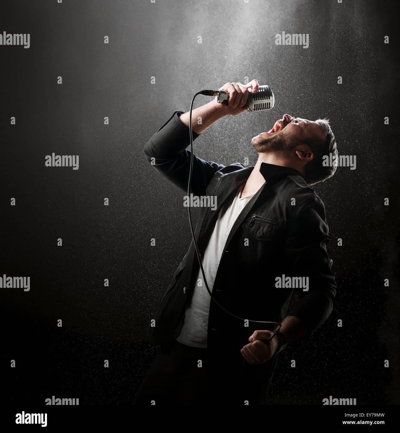 Sänger mit Rauch und Pulver-Anzeige im Hintergrund (Stan Kruger von der Band Leven) Stockbild