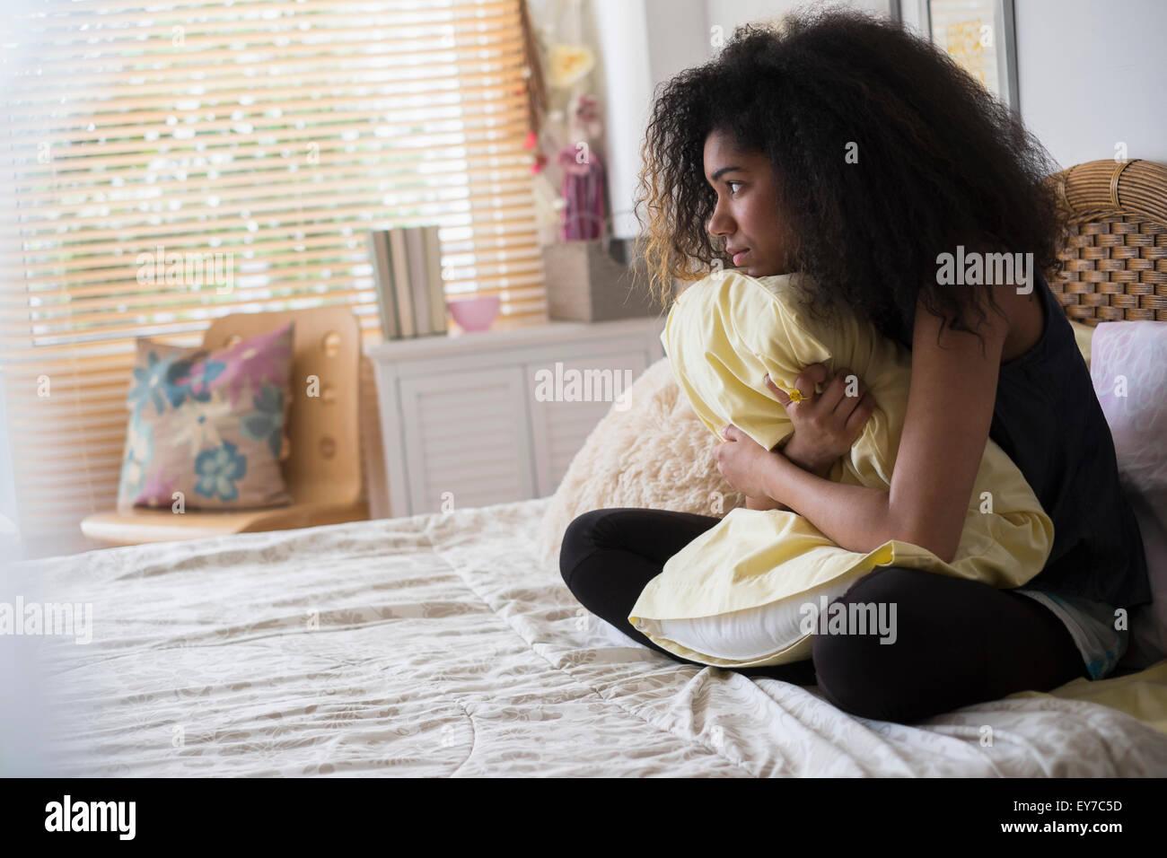 Teenager-Mädchen (14-15) sitzt auf Bett, Kissen umarmen Stockbild