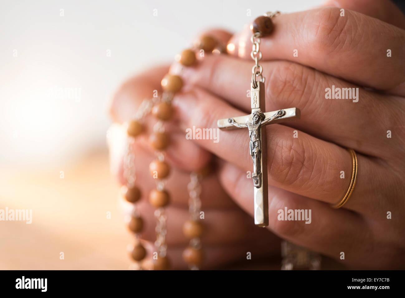 Frau mit Rosenkranz in Händen beten Stockbild