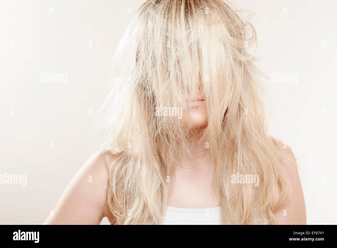 Junge Frau, blondes Haar bedeckte Gesicht Stockbild
