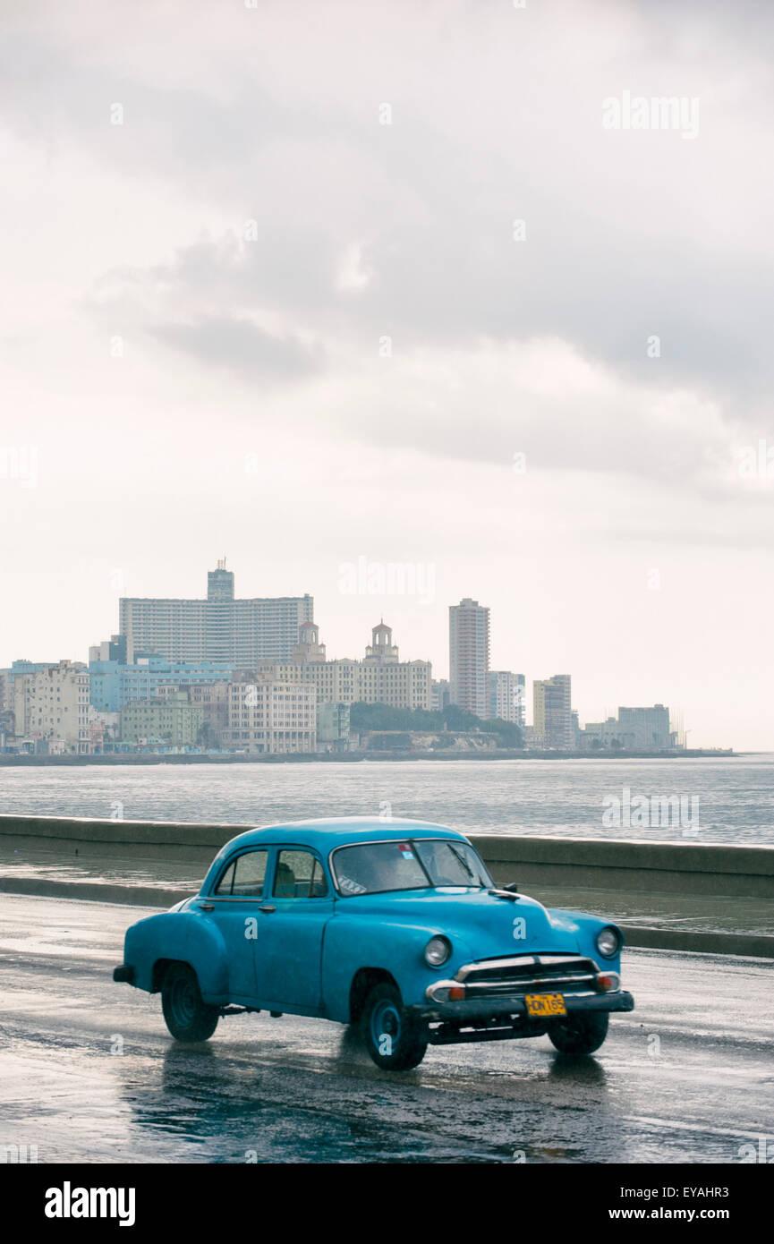 Havanna, Kuba - 13. Juni 2011: Old fashioned 50er Jahre Oldtimer geht vor der Skyline der Stadt entlang der Küstenstraße Stockbild