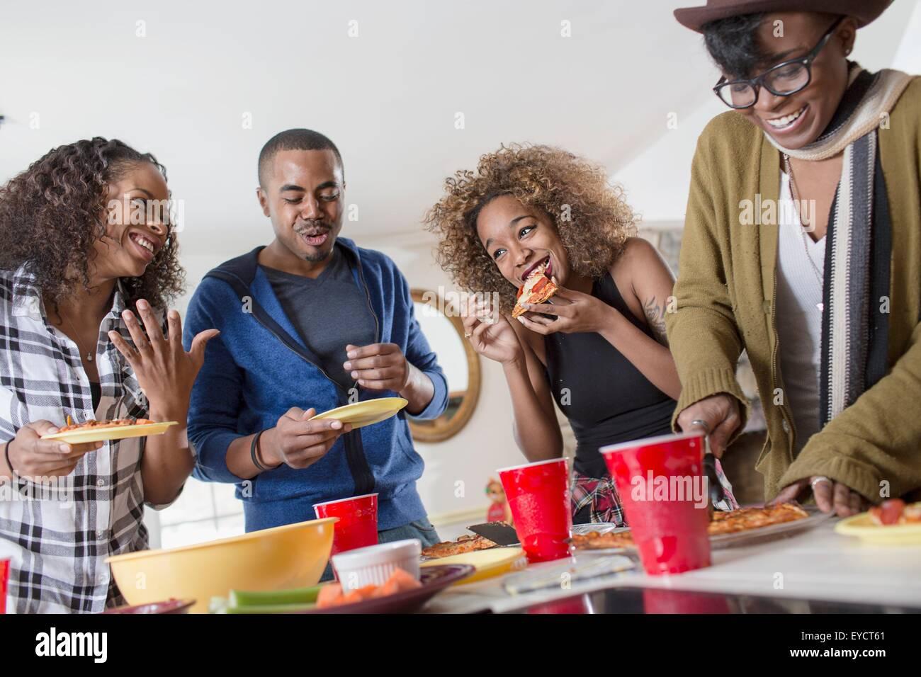 Vier Erwachsene Freunde, chatten und Party Essen in Küche Stockbild