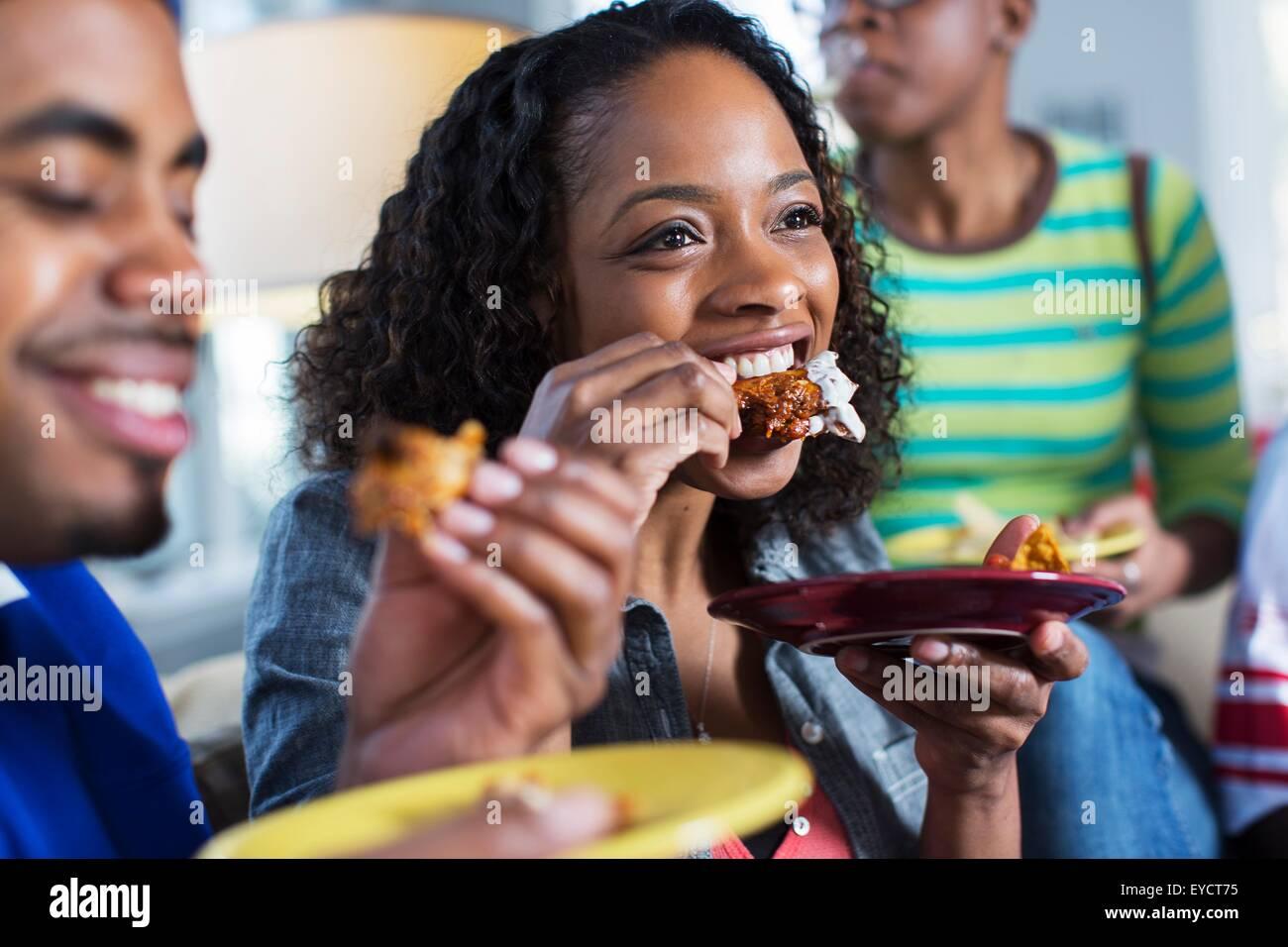 Drei Erwachsene Freunde, Essen zum mitnehmen auf Sofa im Wohnzimmer Stockbild