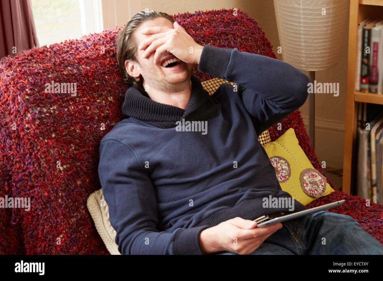 Junger Mann auf Sofa bedeckte sein Gesicht während lachen Stockbild