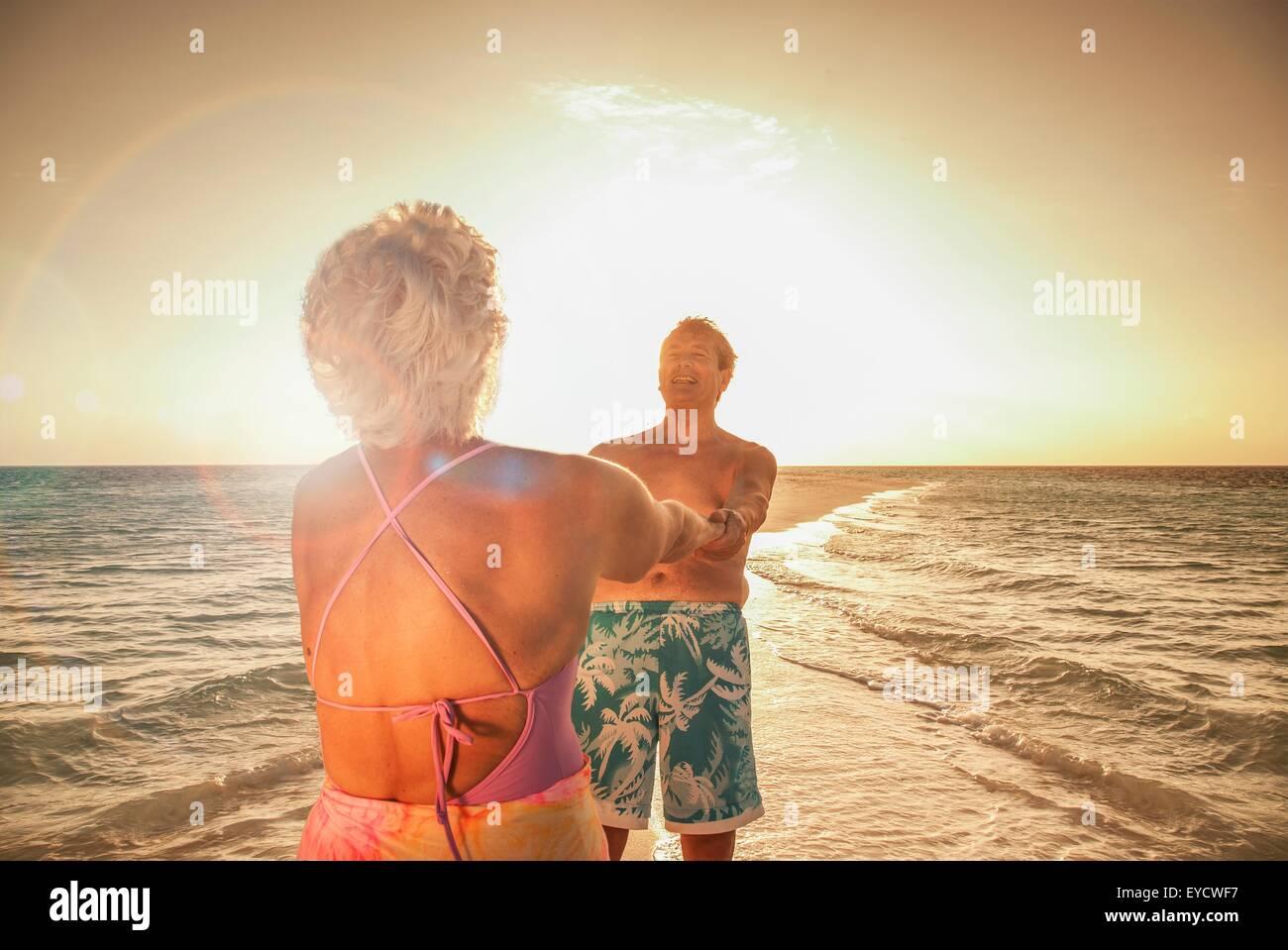 Älteres Paar halten die Hände am Strand Stockbild