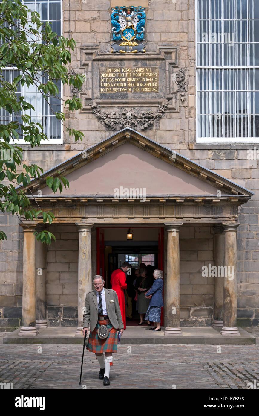 Ein Gemeindemitglied gekleidet in einem Kilt verlassen die Canongate Kirk in Edinburgh nach dem Gottesdienst am Stockbild