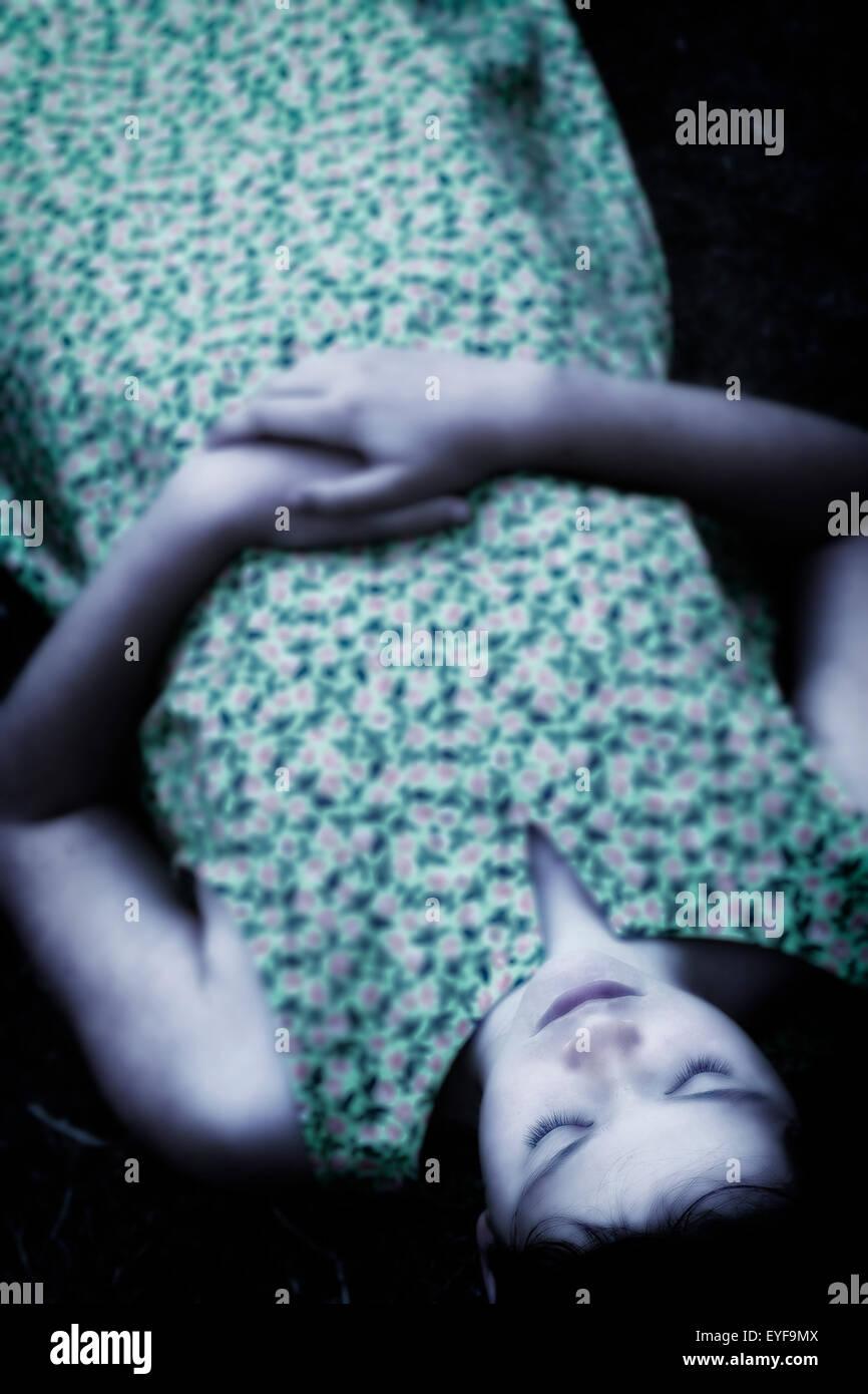 ein Mädchen mit geschlossenen Augen auf dem Boden liegend Stockbild