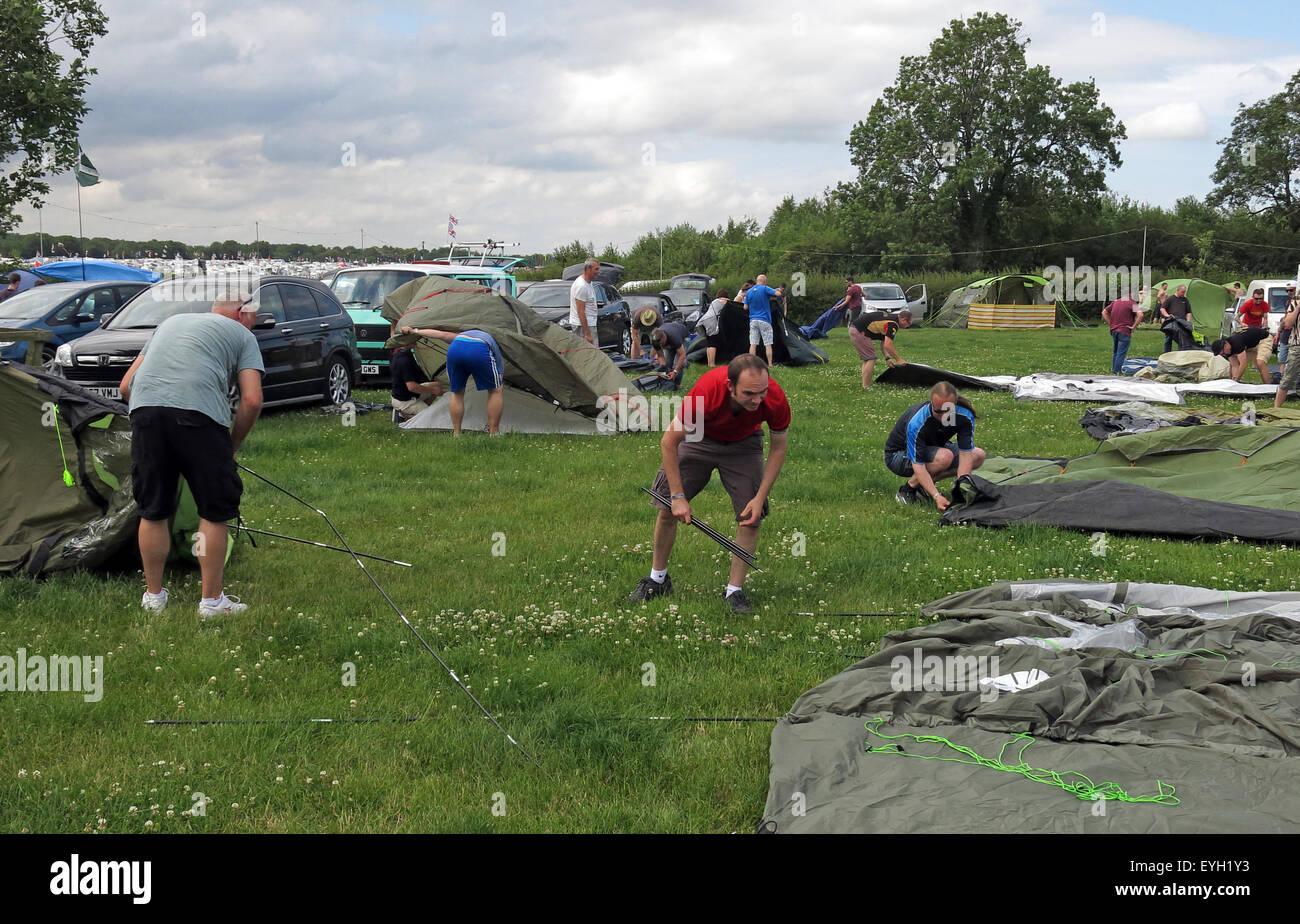 Laden Sie dieses Alamy Stockfoto Irgendwelche Leute, die das Aufstellen von Zelten in einem Feld - EYH1Y3