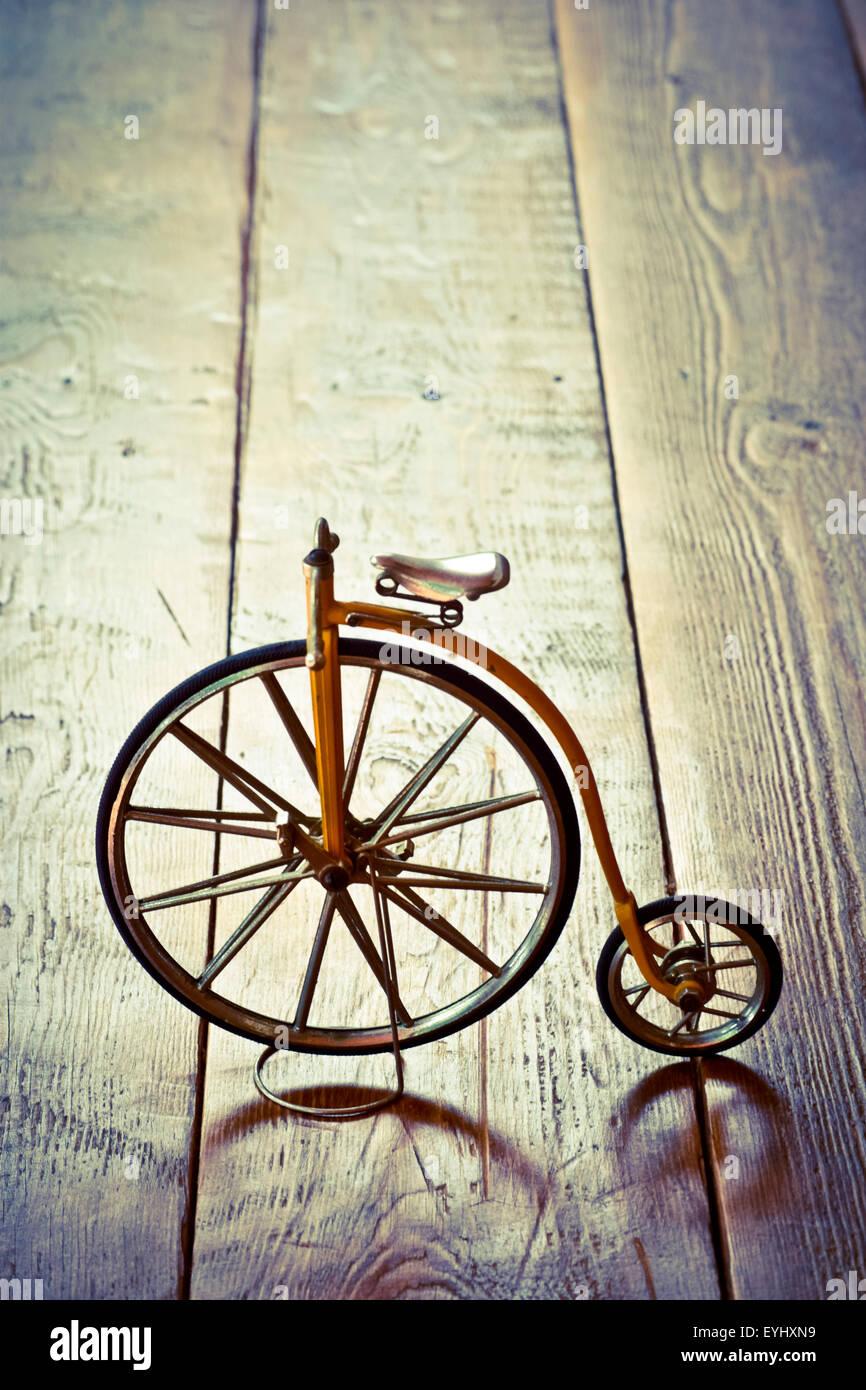Altes Fahrrad mit großen und kleinen Rad auf eine Holzoberfläche. Stockbild