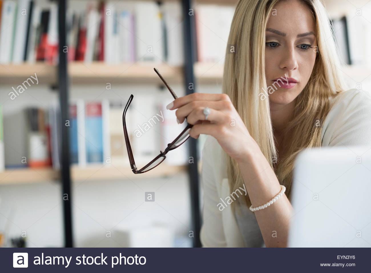Ernsthafte Geschäftsfrau hält Brillen mit laptop Stockbild