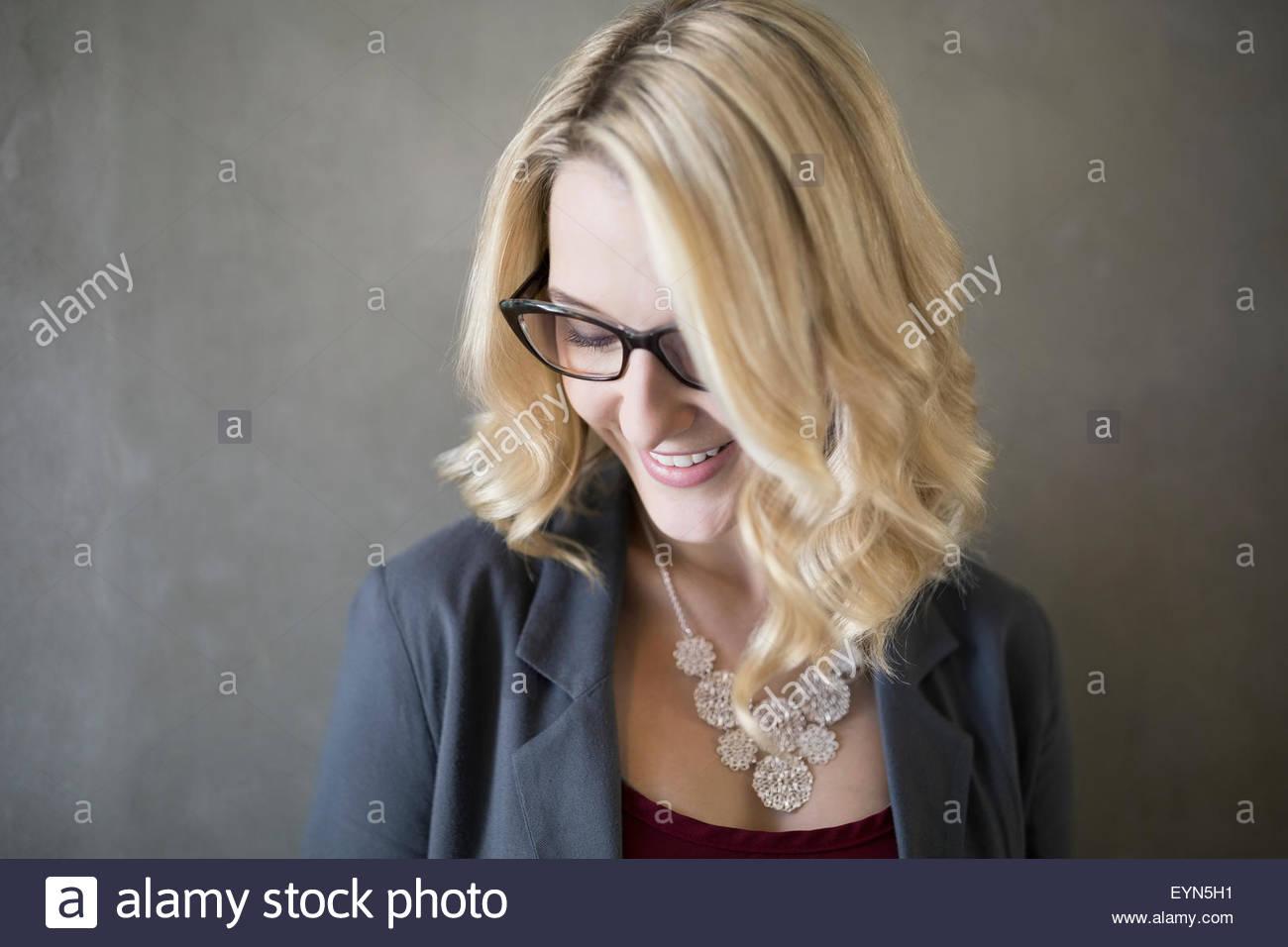 Porträt lächelnden blonden Geschäftsfrau mit Brille schaut Stockbild