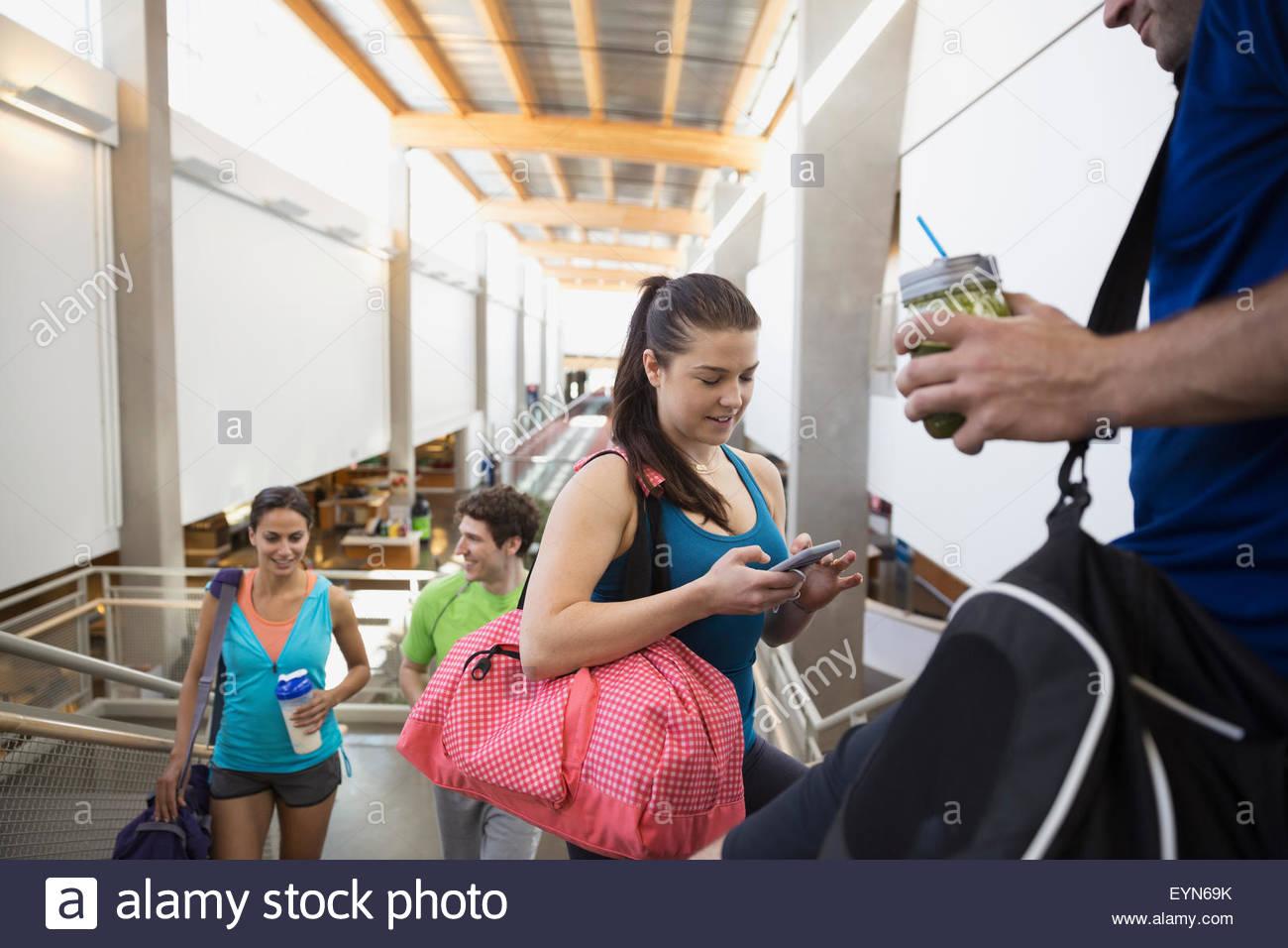 Freunde sprechen und mit Handy in Turnhalle Stockfoto