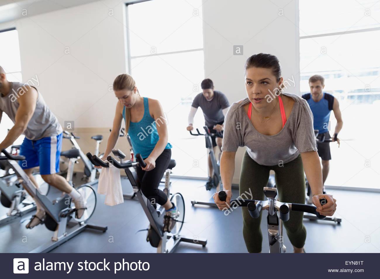 Spin-Klasse auf stationären Fahrrädern in Turnhalle Stockfoto