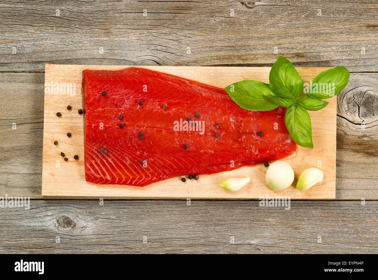Ansicht von oben Schuss von frischen roten Lachs Filet am Cedar Kochen Board mit Pfeffer, Knoblauch und Basilikum. Stockbild