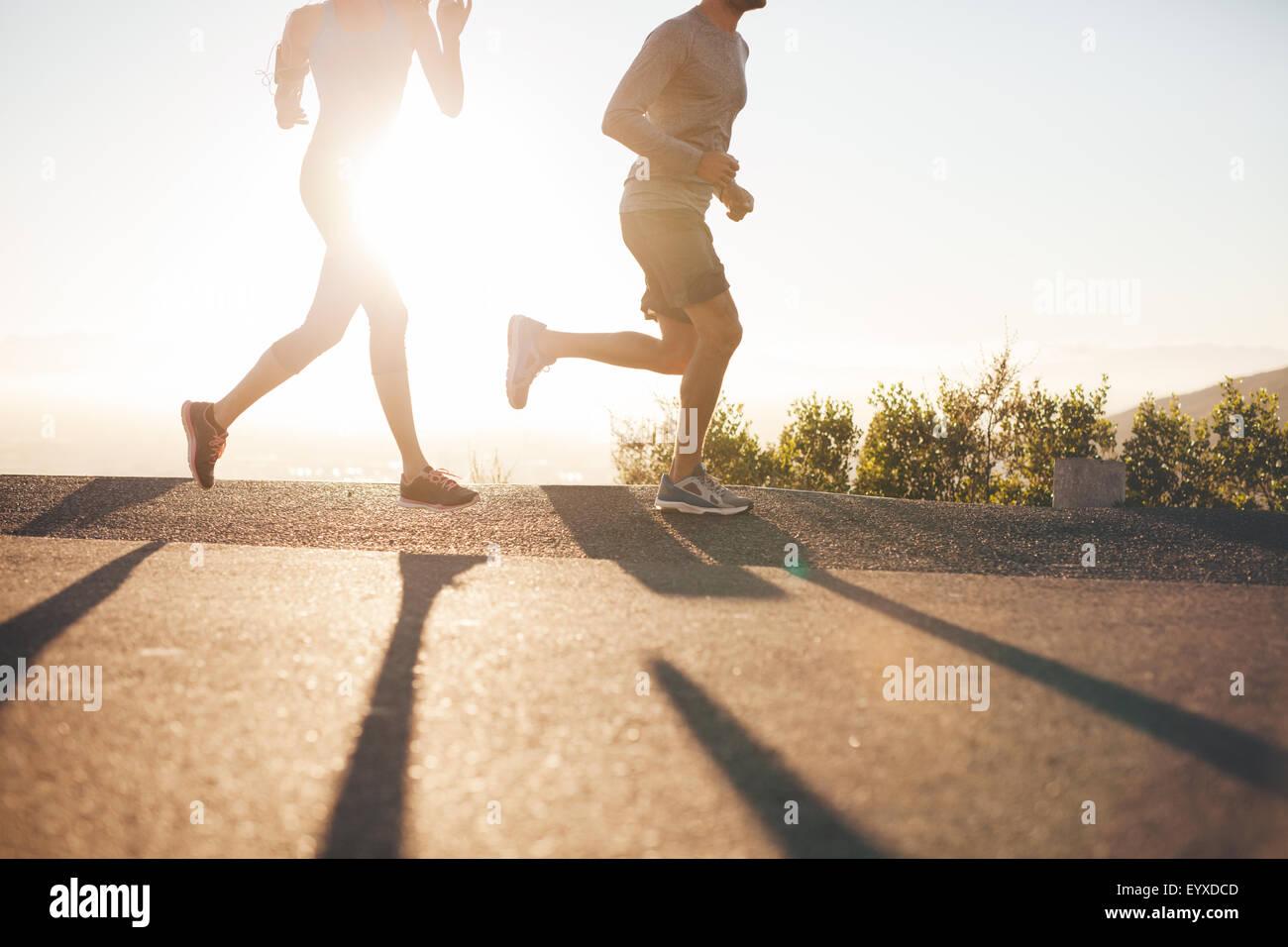 Niedrigen Winkel Blick auf zwei Menschen laufen auf Landstraße bei Sonnenaufgang. Schuss von junger Mann und Stockbild