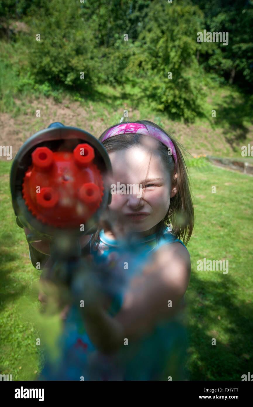 Junges Mädchen schießen Wasserpistole in ihrem Garten. Stockbild