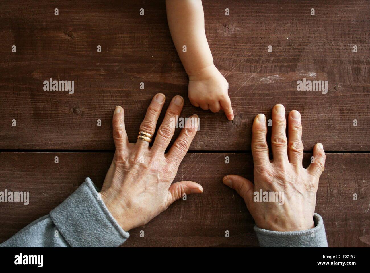 Baby Hand des jungen auf Großmutters Hände zeigen Stockbild