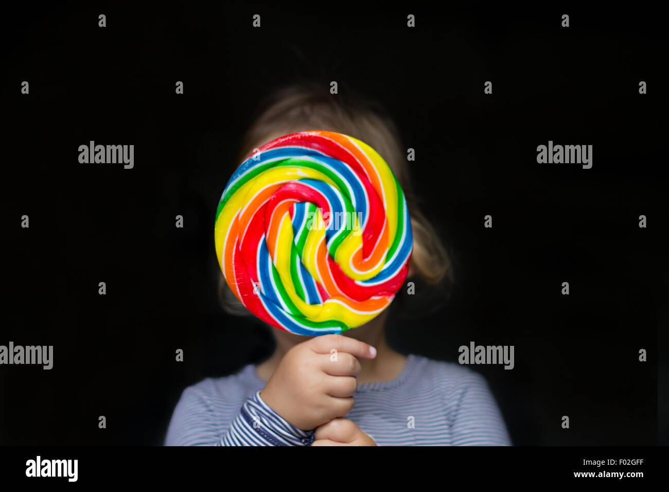 Porträt eines Mädchens hält einen bunten lollipop Stockbild