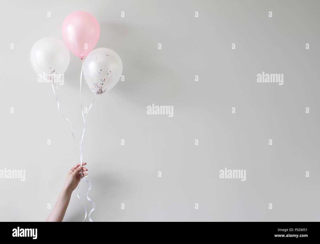 Hand, die Luftballons mit Konfetti im Inneren Stockbild