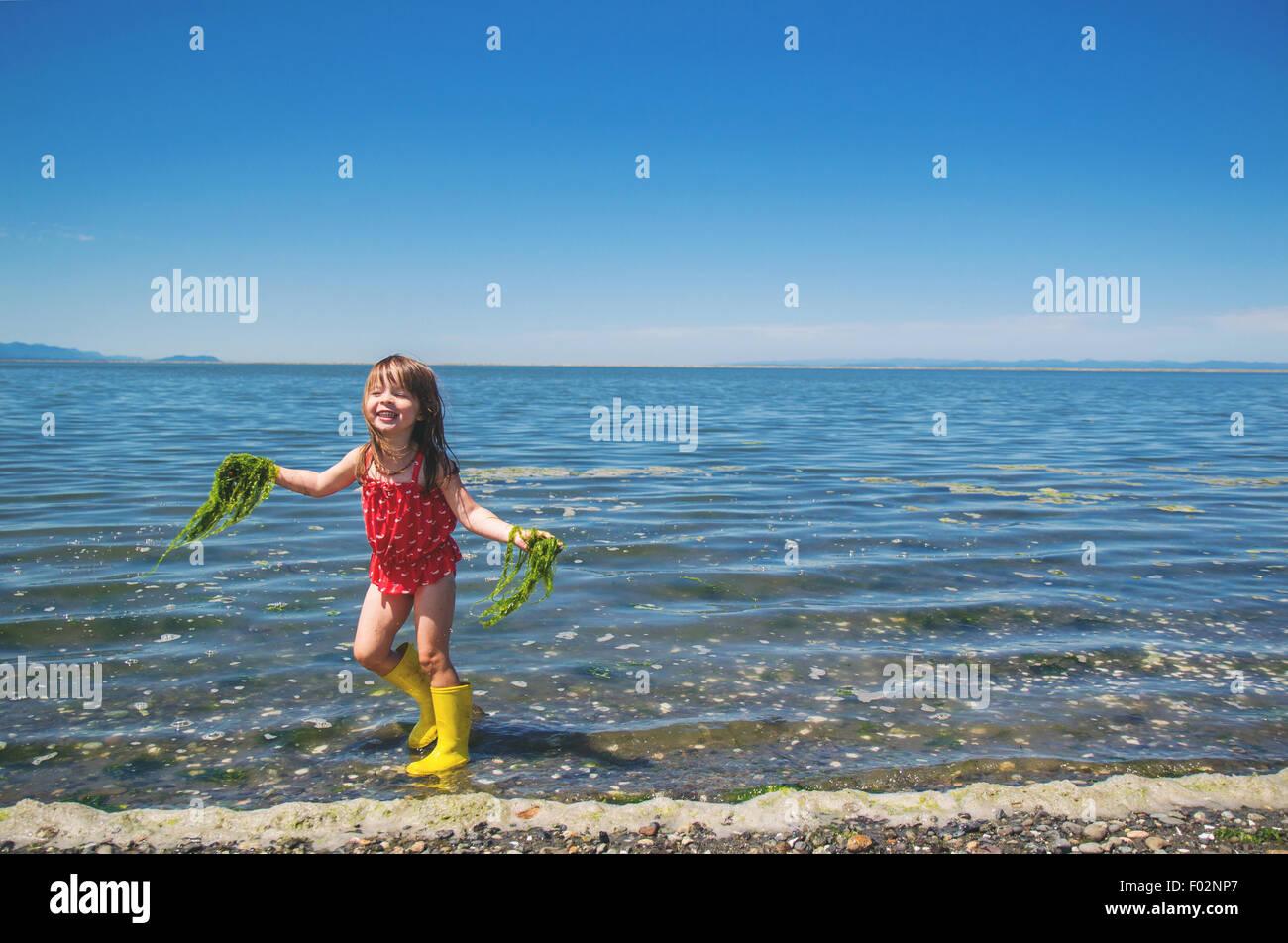 Mädchen sammeln Algen aus dem Meer Stockbild