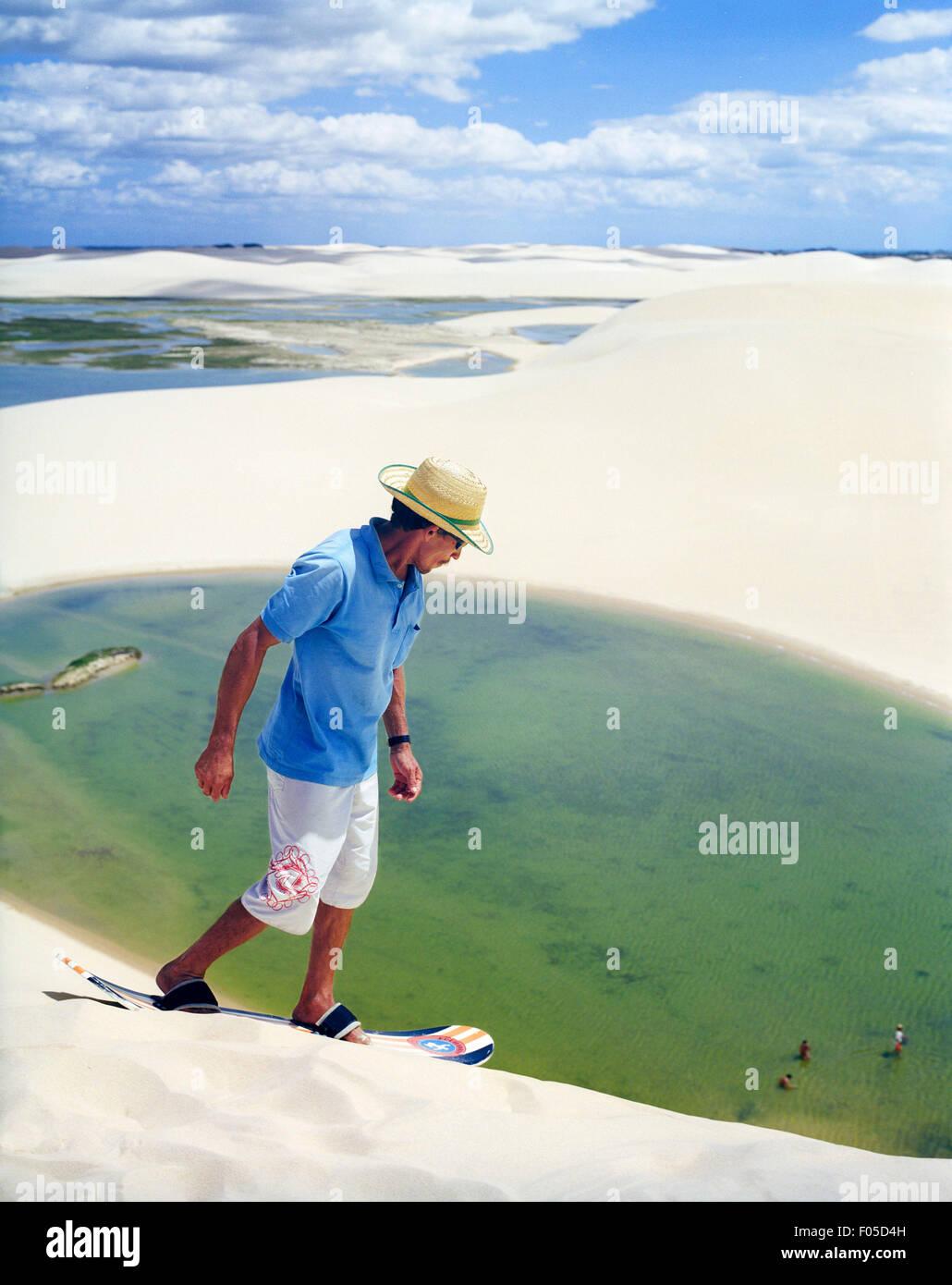 Ein brasilianischer Mann klettert eine Düne zu einem anderen laufen Sand boarding auf einer Düne am Dunas Stockbild