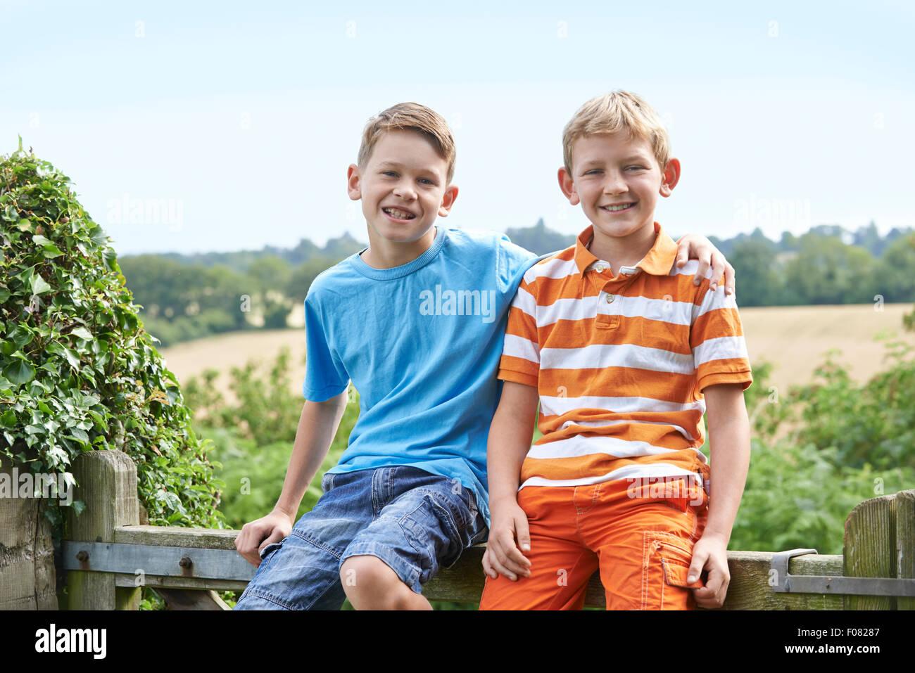Porträt von zwei jungen Zusammensitzen auf Tor Stockbild