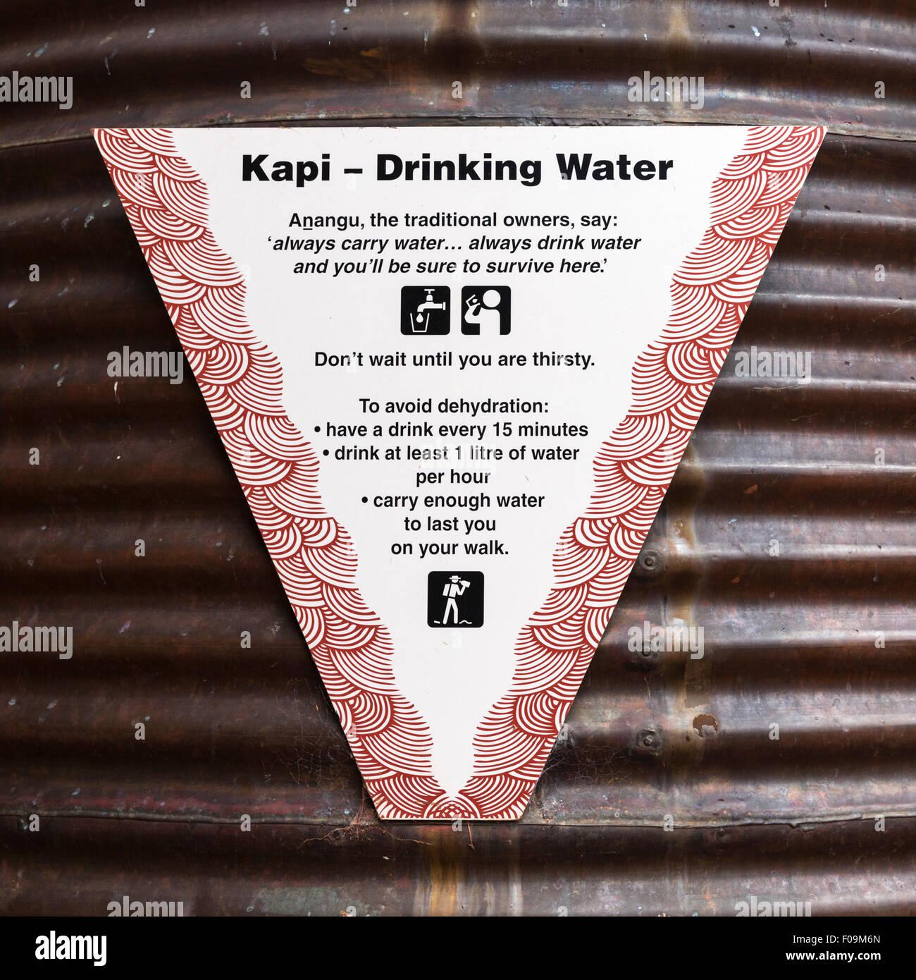 Wasser Tank Schild am Kulturzentrum in Uluru-Kata Tjuta National Park empfiehlt trinken 1 Liter pro Stunde, um Austrocknung Stockbild