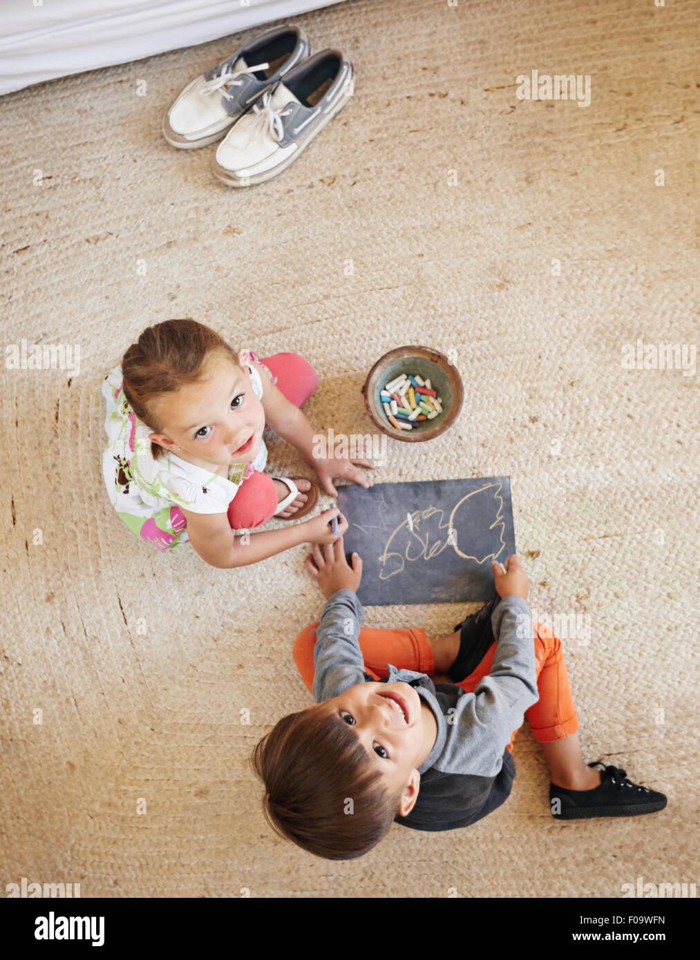 Draufsicht der zwei kleine Kinder sitzen am Boden nach oben auf die Kamera während des Zeichnens. Stockbild