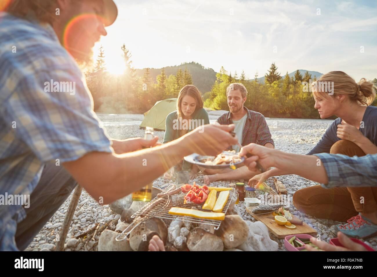 Erwachsene sitzen am Lagerfeuer, die Speisen vom Grill Stockbild