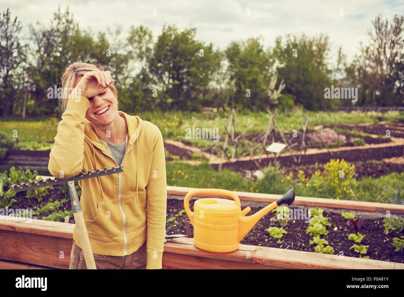 Reife Frau, Gartenarbeit, stützte sich auf Rechen, lachen Stockbild