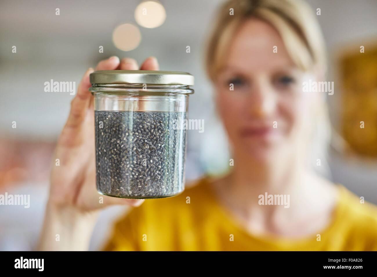 Reife Frau hält Glas Samen, Samen im Fokus Stockbild