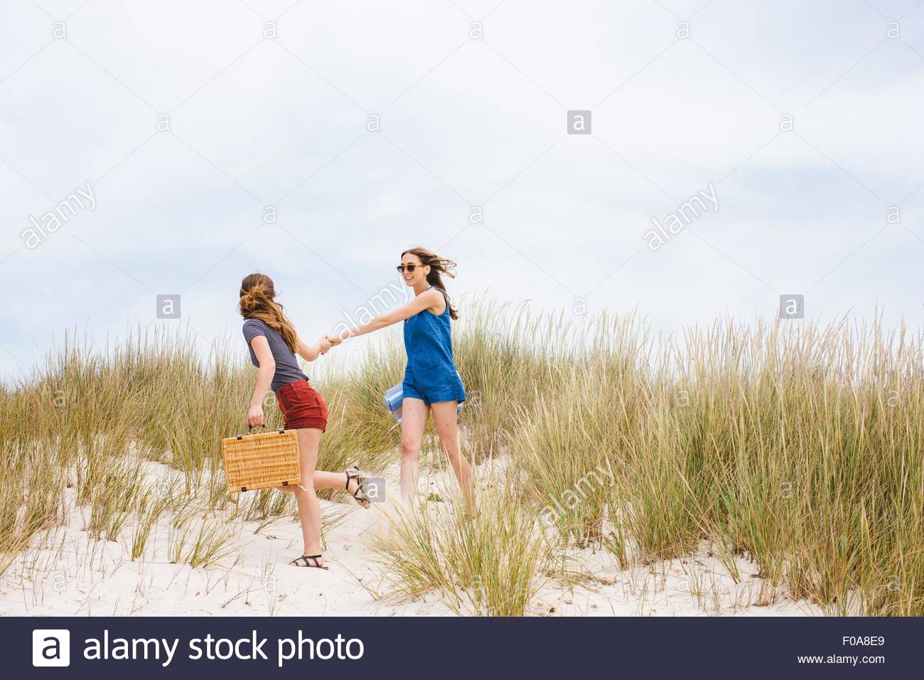 Zwei junge Freundinnen Picknick Korb Hand in Hand auf Sanddünen Stockbild