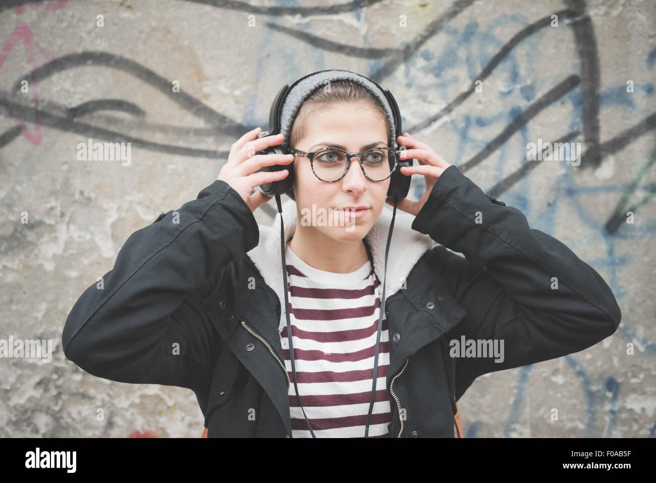 Teenager mit Kopfhörer von Graffitiwand Stockbild