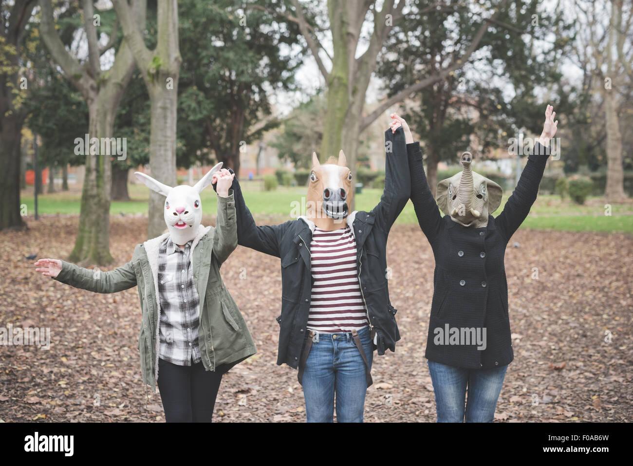 Drei Schwestern tragen Masken tanzen im park Stockbild