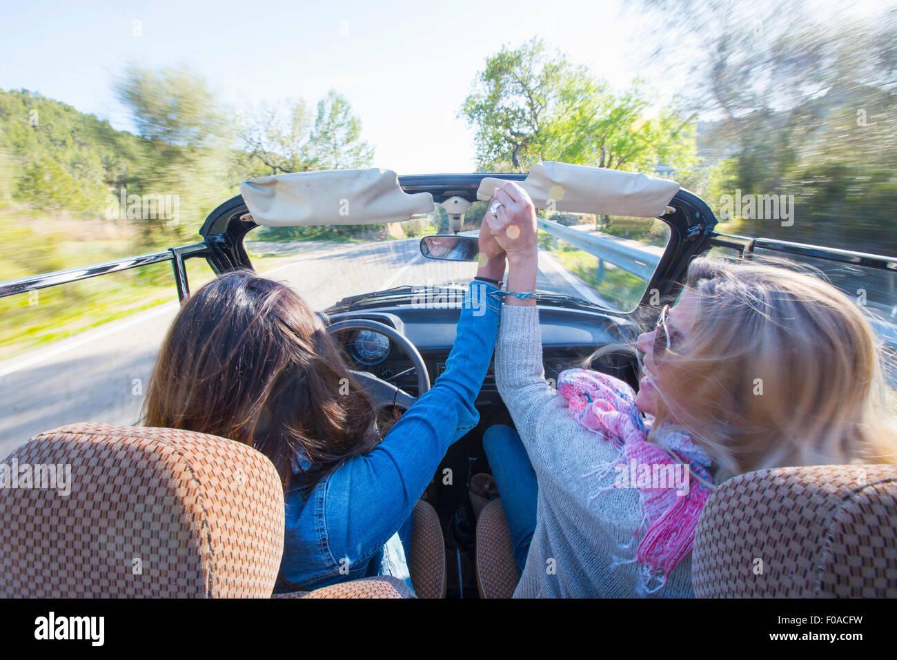 Zwei Reife Frauen, Hand in Hand, im Cabrio, Rückansicht Stockbild