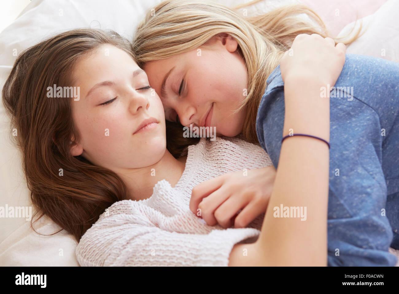 Zwei Mädchen auf dem Bett liegend mit Augen geschlossen Stockbild