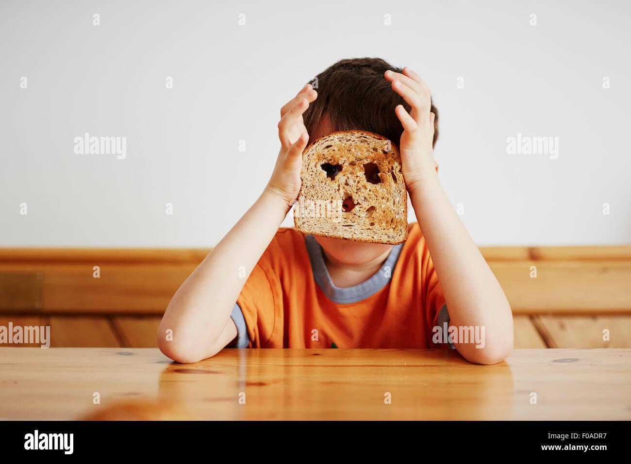 Kleiner Junge für Gesicht mit toast Stockbild