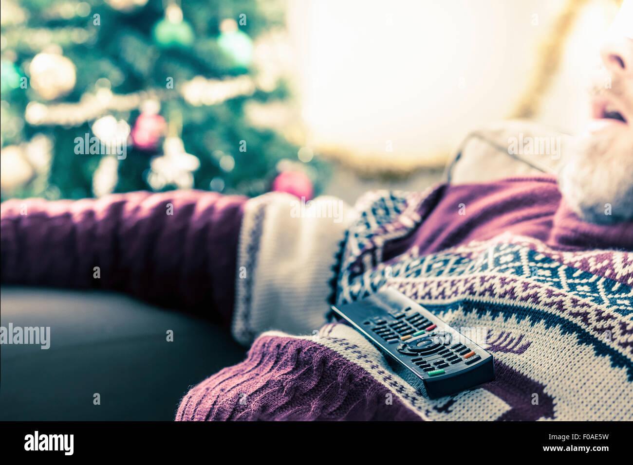 Mann mit Pullover mit Fernbedienung eingeschlafen auf Brust Stockbild