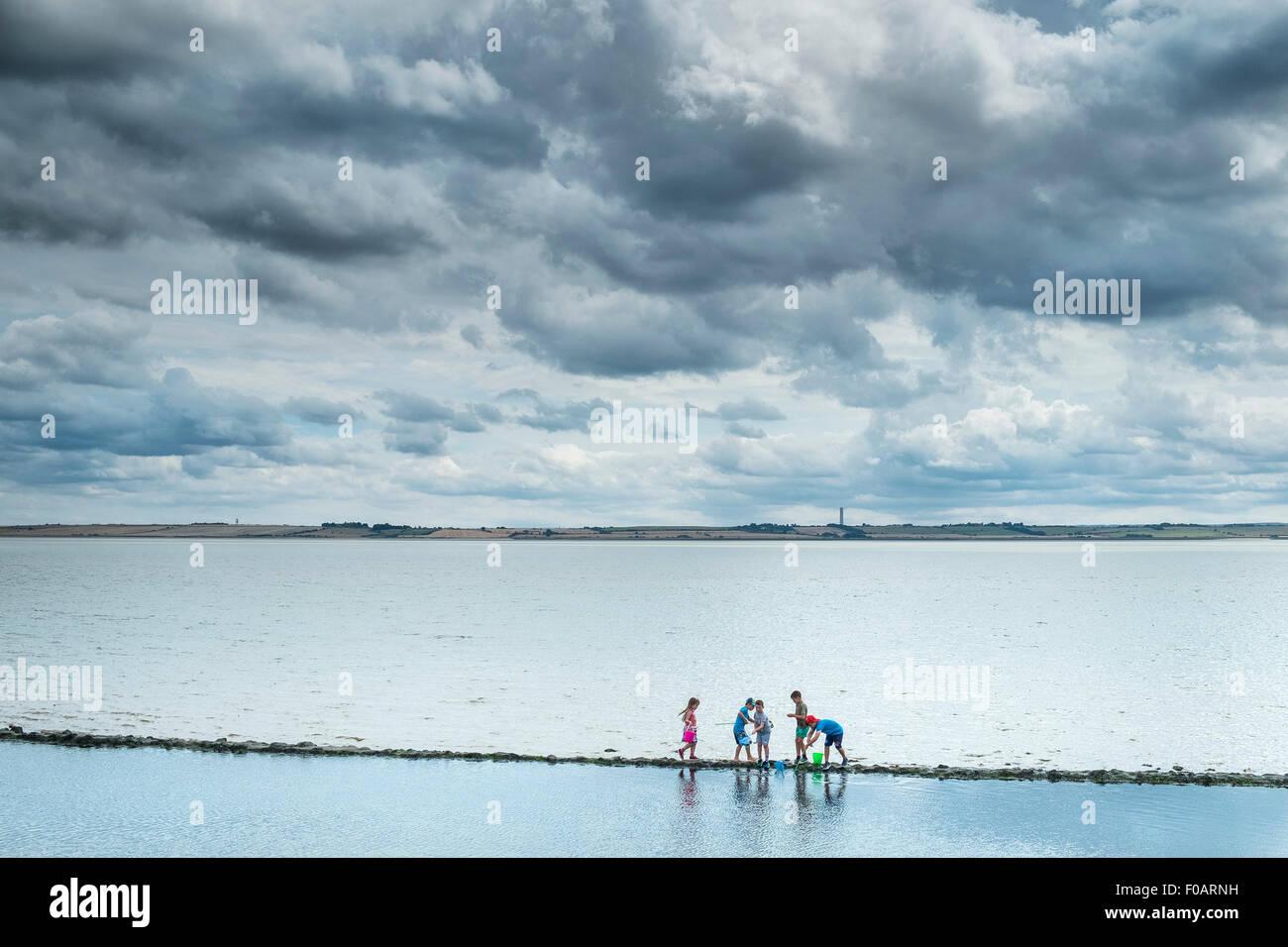 Kinder erkunden auf dem Vorland auf Canvey Island, Essex. Stockbild