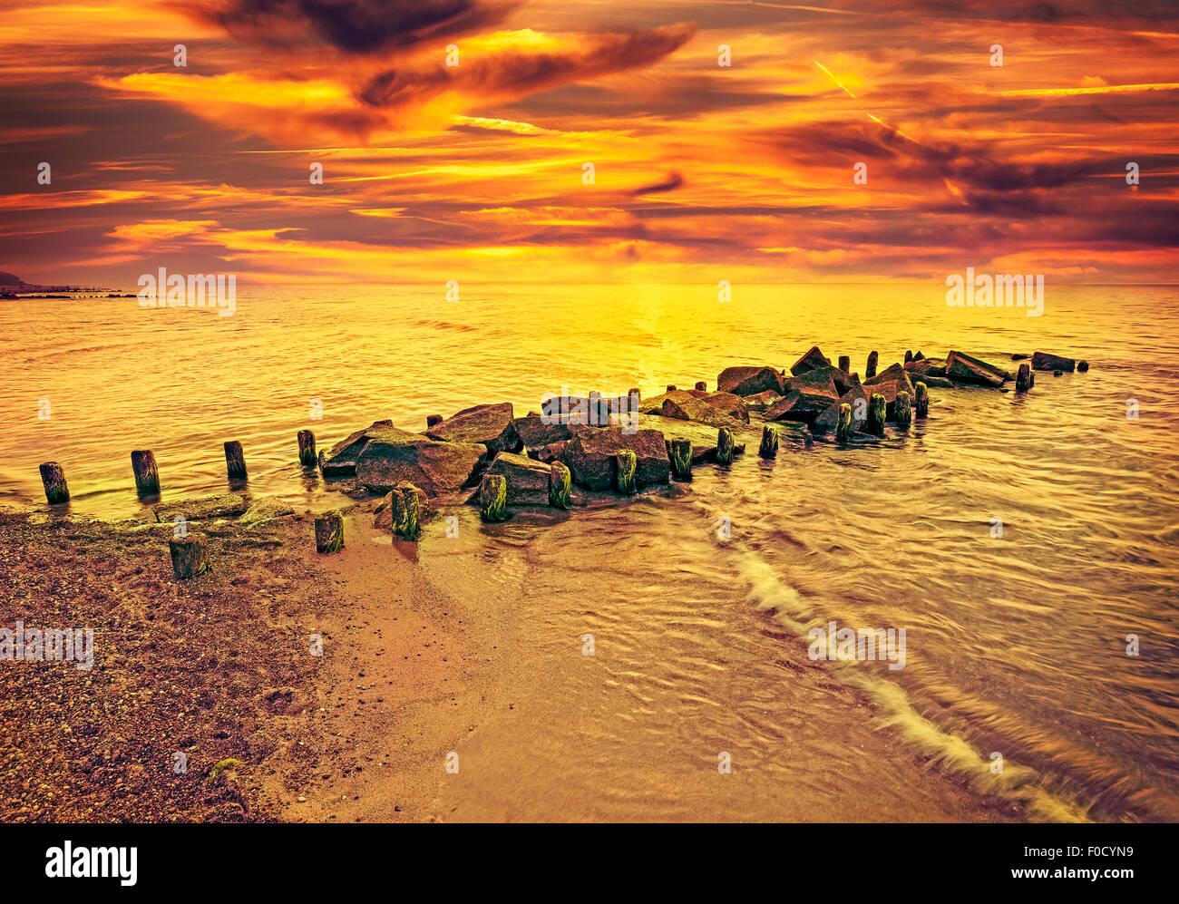 Vintage getönten dramatischen Sonnenuntergang über Strand und felsigen Pier. Stockbild