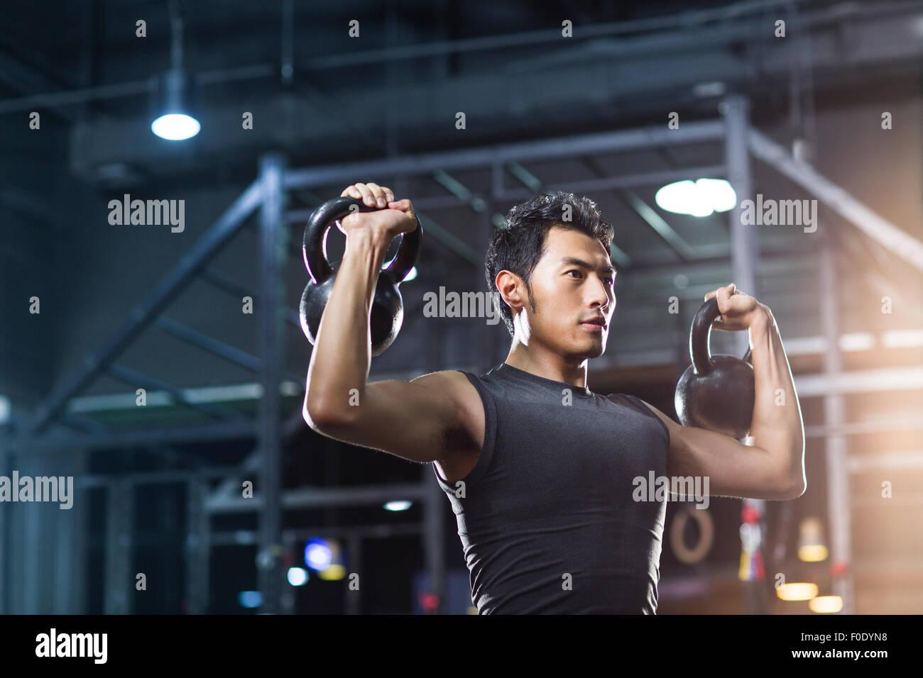 Junger Mann Training mit Kettlebells in Crossfit gym Stockbild