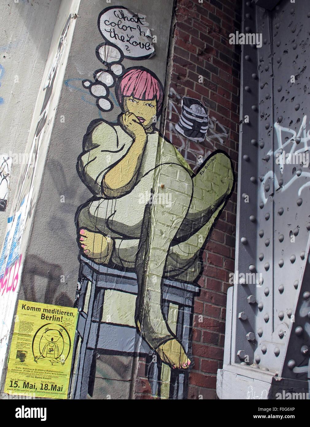 Laden Sie dieses Alamy Stockfoto Berlin-Mitte, Streetart an Wänden, Deutschland - Girl sitzt Crosslegged auf Tisch was Farbe hat die Liebe? - F0G6XP