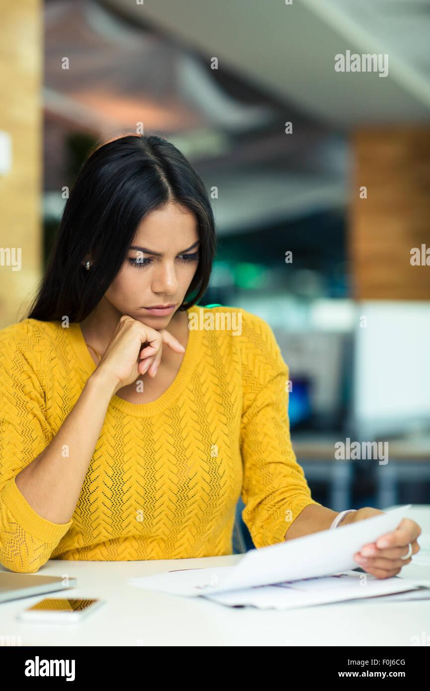Porträt einer schönen Geschäftsfrau, Lesen von Dokumenten im Büro Stockbild