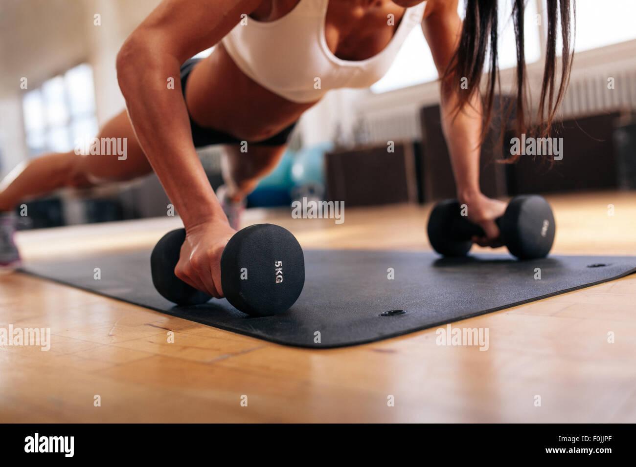 Schuss der muskulöse Frau macht Liegestütze auf Hanteln beschnitten. Weibchen auf Fitness-Matte im Fitnessraum Stockbild