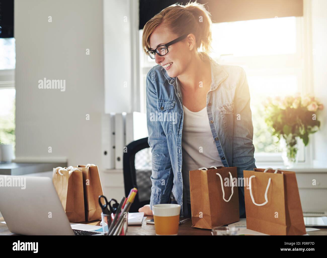 Happy Geschäftsfrau arbeiten im Home Office stehen auf Ihren Laptop durch gift bags umgeben und Verpackung Stockbild