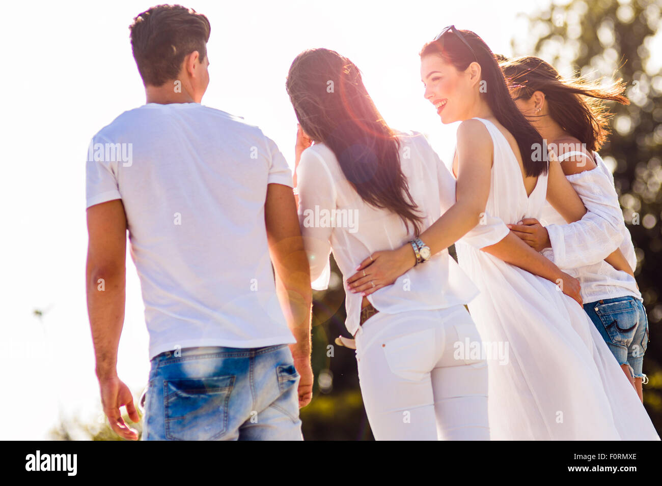 Gruppe von Jugendlichen, die Hand in Hand am Strand als Zeichen der Freundschaft Stockbild